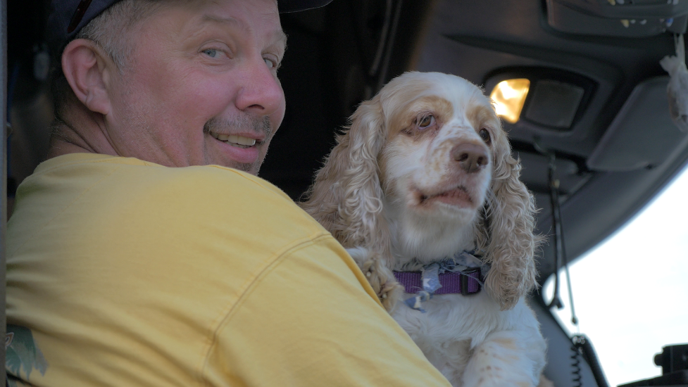 A man in a yellow shirt holds a small dog in the cab of a semi truck.